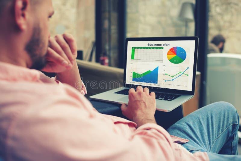 Empresário novo que analisa o desempenho em seu caderno imagens de stock