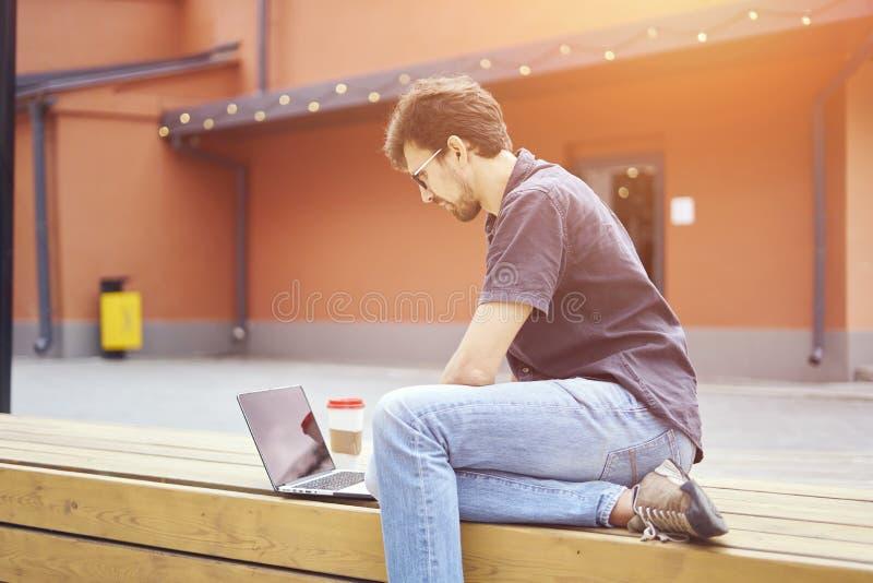 Empresário novo que trabalha no parque fora no banco de madeira Homem que usa o portátil, escrevendo o texto Opinião da rua Conce foto de stock