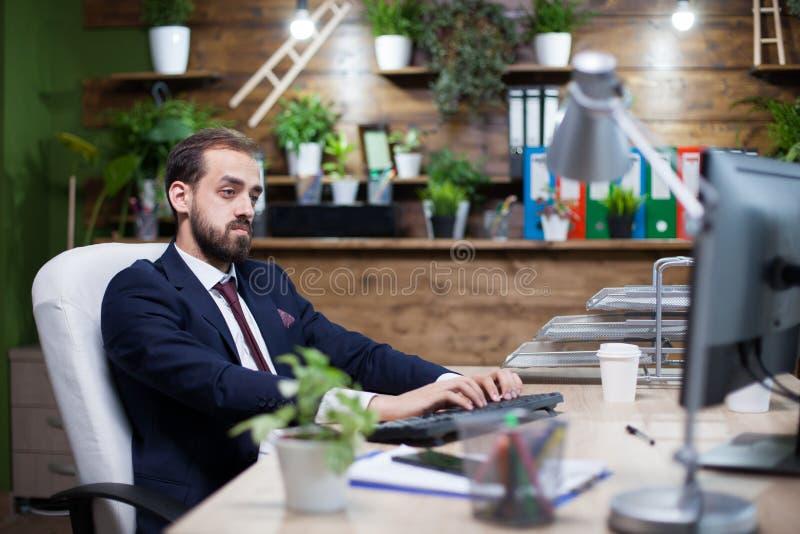 Empresário novo sério que trabalha no computador em seu escritório foto de stock royalty free