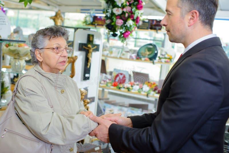 Empresário que agita a senhora das pessoas idosas da mão imagens de stock