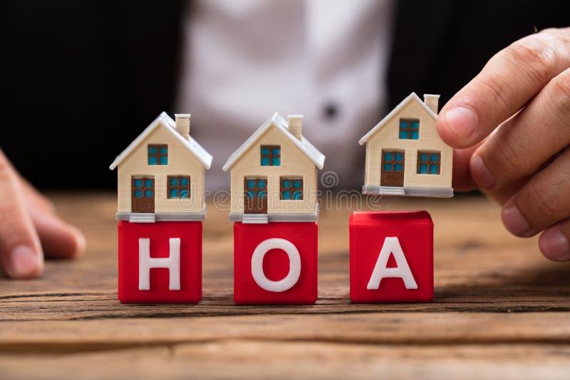Empresário que coloca o modelo da casa sobre blocos de HOA foto de stock