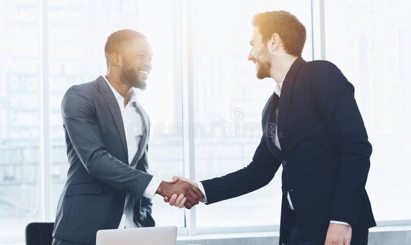 Empresário que dá boas-vindas ao empregado novo e que agita a mão fotografia de stock