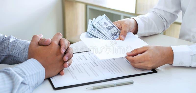 Empresário que dá dinheiro para suborno no envelope do seu parceiro para dar sucesso ao contrato de negócio numa fraude de corrup imagens de stock