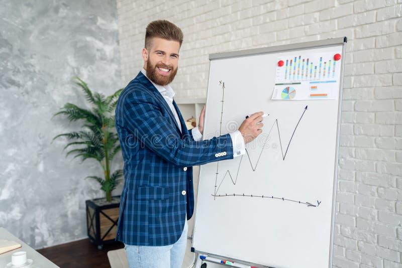 Empresário que faz uma apresentação no escritório Empreendedor que usa o quadro para apresentar ideias para planejamento e decisã fotos de stock
