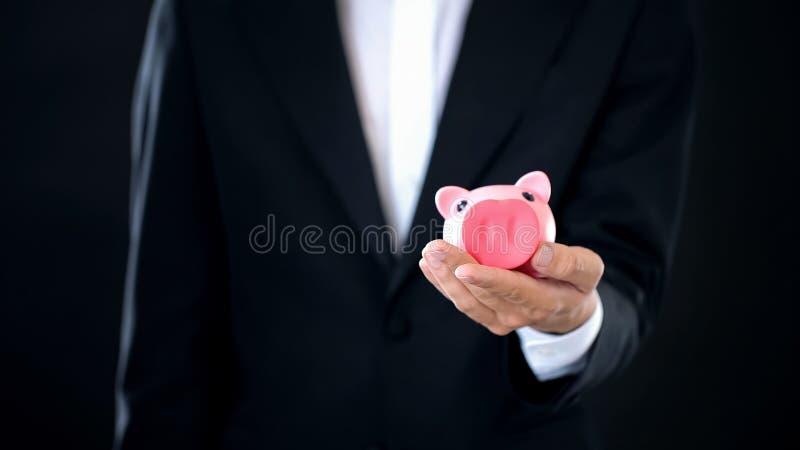 Empresário que guarda o piggybank à disposição, conta poupança, renda do depósito bancário imagens de stock royalty free