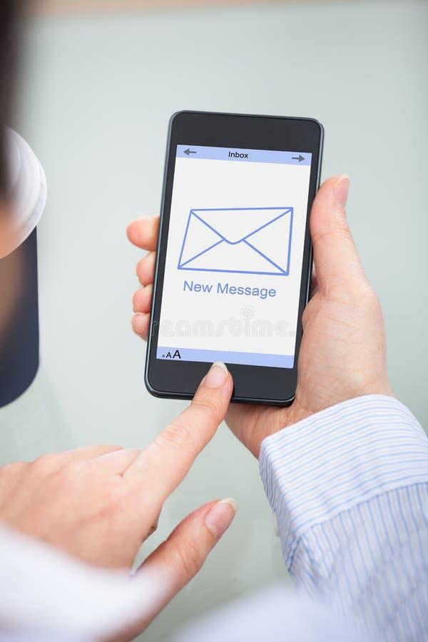 Empresário que guarda o telefone celular com sinal novo da mensagem imagem de stock