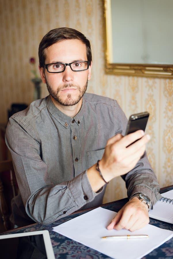 Empresário que trabalha em casa e que envia a mensagem no telefone esperto foto de stock royalty free