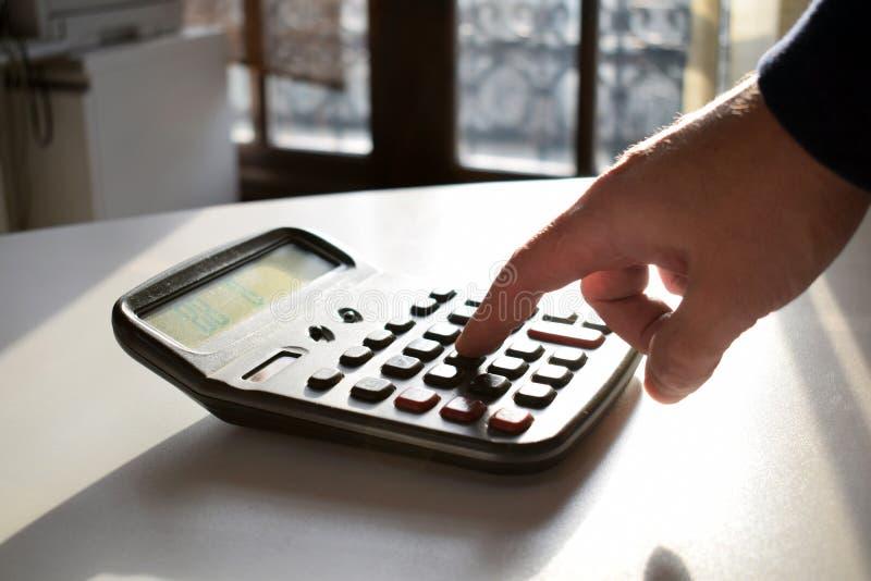 Empresário que trabalha no escritório Mão do homem com a calculadora no local de trabalho imagem de stock royalty free