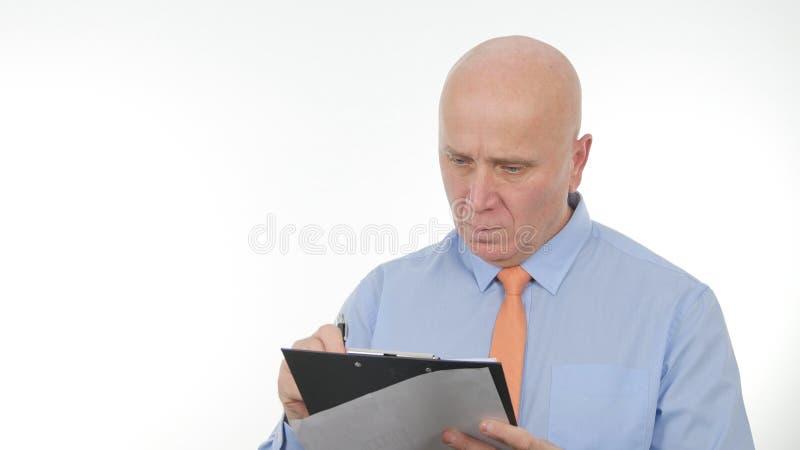 Empresário Read e para escrever em um documento usando uma prancheta imagem de stock royalty free
