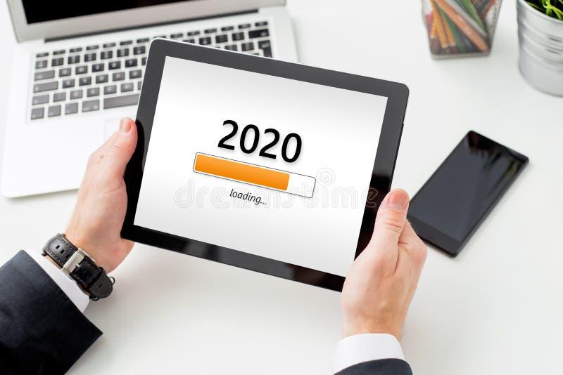 Empresário segurando tablet com carregamento no ecrã no ano de 2020 foto de stock royalty free