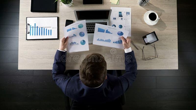 Empresário sobrecarregado que senta-se na tabela e que compara dois gráficos, vista superior imagens de stock