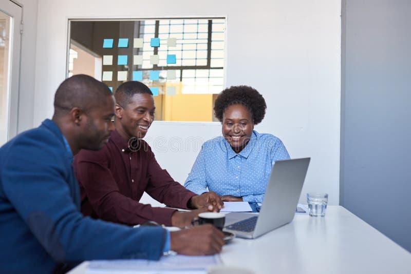 Empresários africanos novos de sorriso que trabalham em um portátil junto imagens de stock royalty free