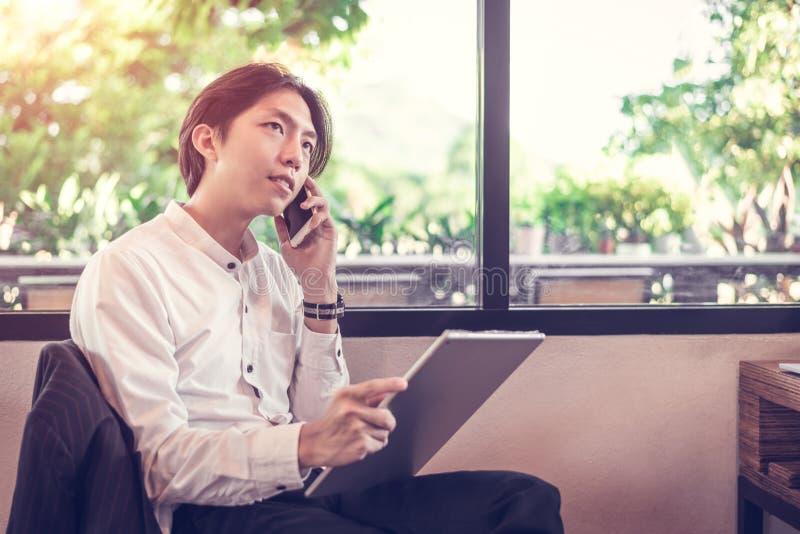 Empresários asiáticos estão falando ao telefone sobre trabalho, Relaxe, use o computador na cafeteria imagem de stock