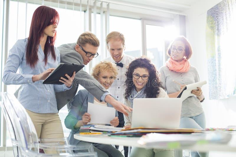 Empresários criativos de sorriso que trabalham no portátil na mesa no escritório imagem de stock