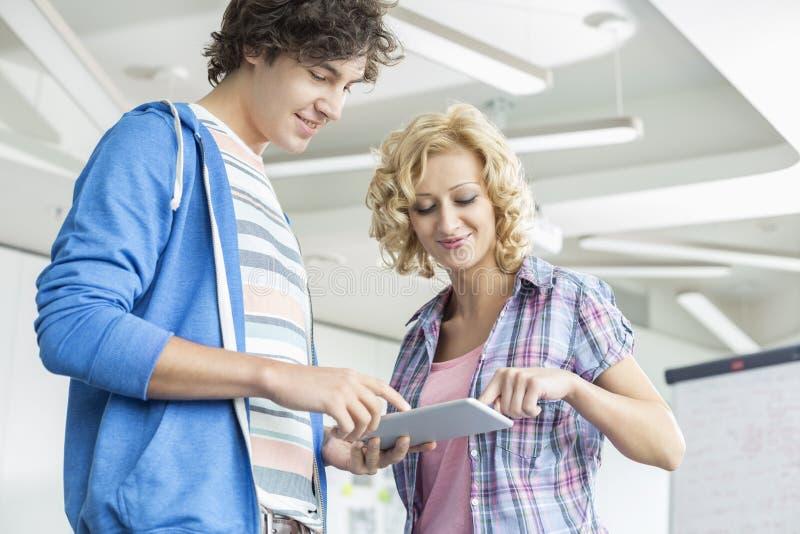 Empresários criativos que usam o PC da tabuleta junto no escritório imagens de stock