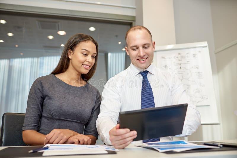 Empresários de sorriso com o PC da tabuleta no escritório fotos de stock