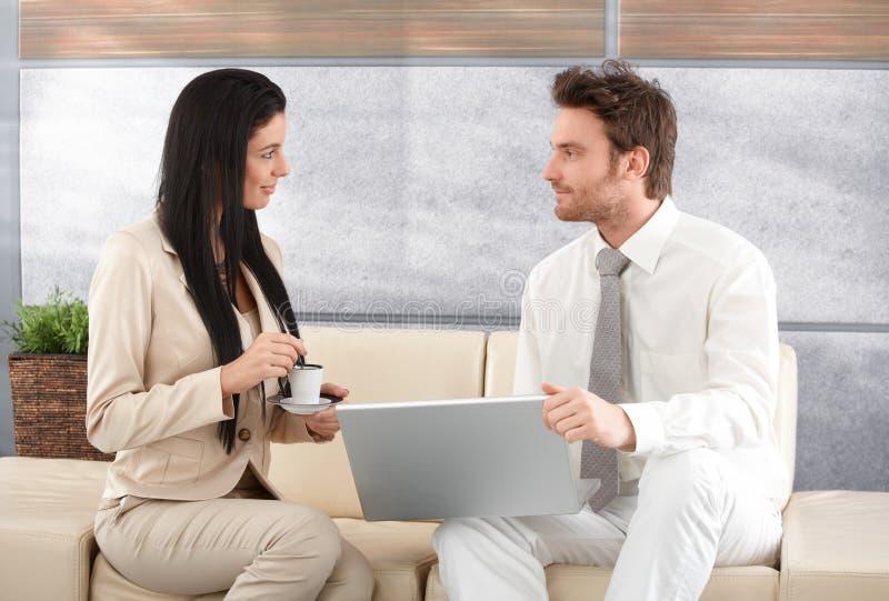 Empresários elegantes que usam a fala do portátil imagens de stock royalty free