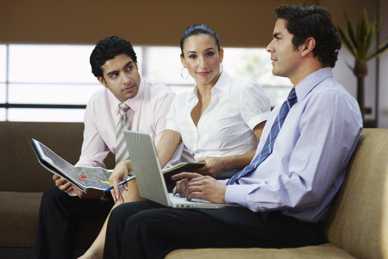 Empresários em Sofa During Meeting imagem de stock