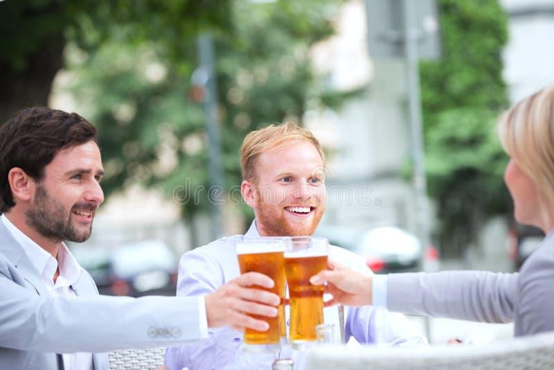 Empresários felizes que brindam vidros de cerveja no restaurante exterior fotografia de stock