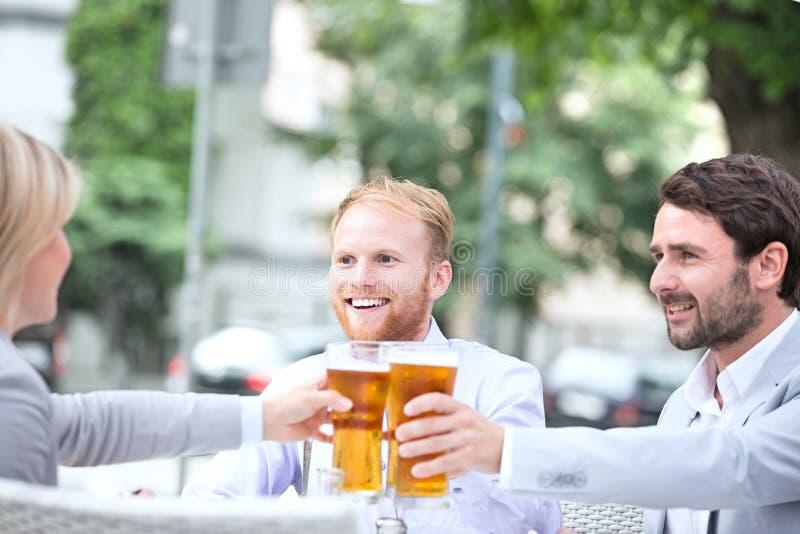 Empresários felizes que brindam vidros de cerveja no restaurante exterior foto de stock royalty free