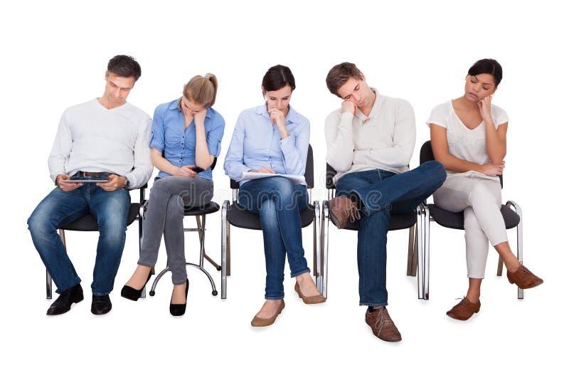 Empresários furados que sentam-se em cadeiras imagem de stock