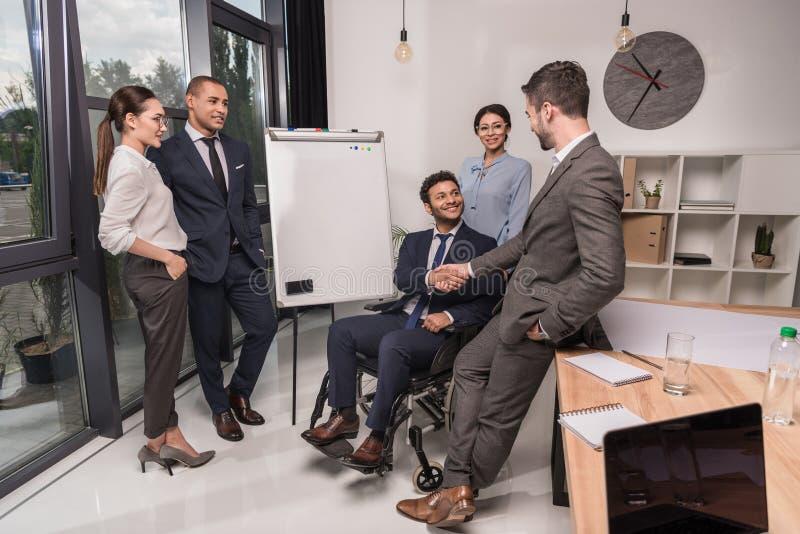 empresários multiculturais que agitam as mãos após ter encontrado colegas imagens de stock