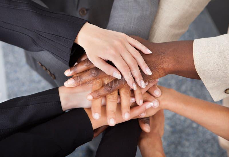 Empresários multirraciais que empilham as mãos imagem de stock
