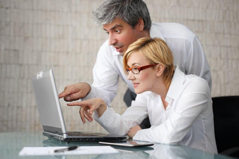 Empresários novos bem sucedidos com portátil imagens de stock