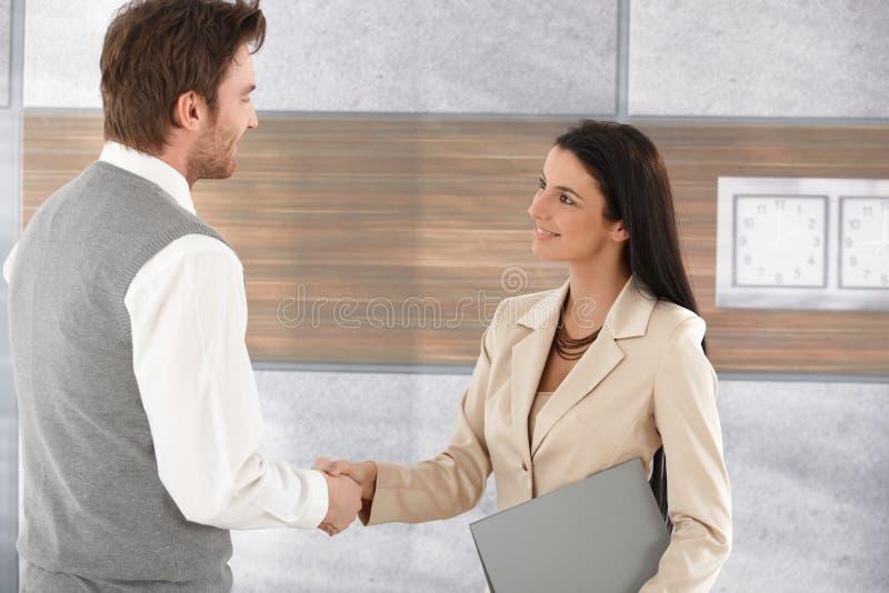 Empresários novos que agitam o sorriso das mãos imagem de stock