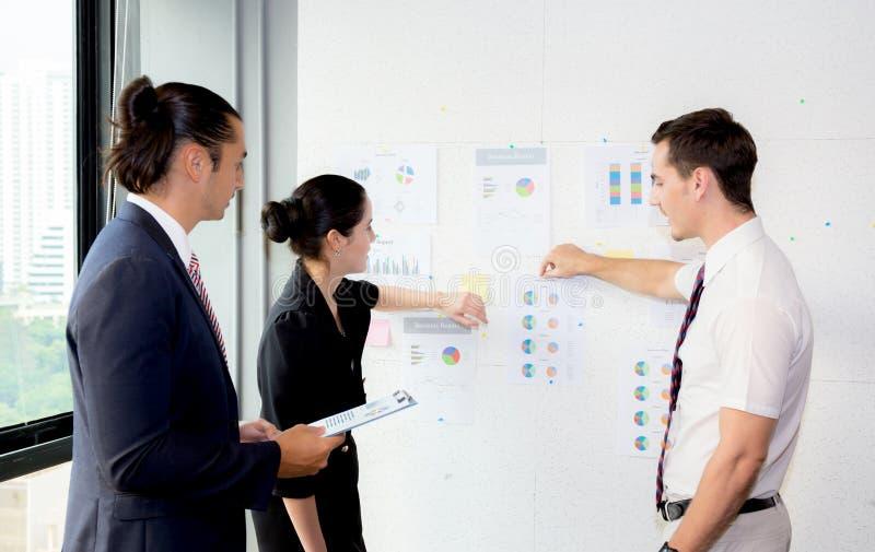 Empresários novos que apontam para o gráfico com lucro atual ao dar a apresentação no escritório imagens de stock royalty free