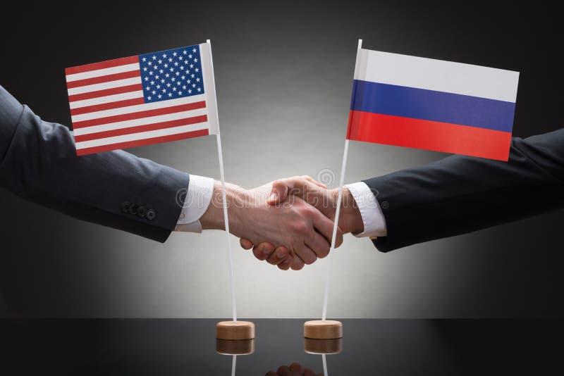 Empresários que agitam as mãos connosco e as bandeiras de Rússia fotografia de stock royalty free