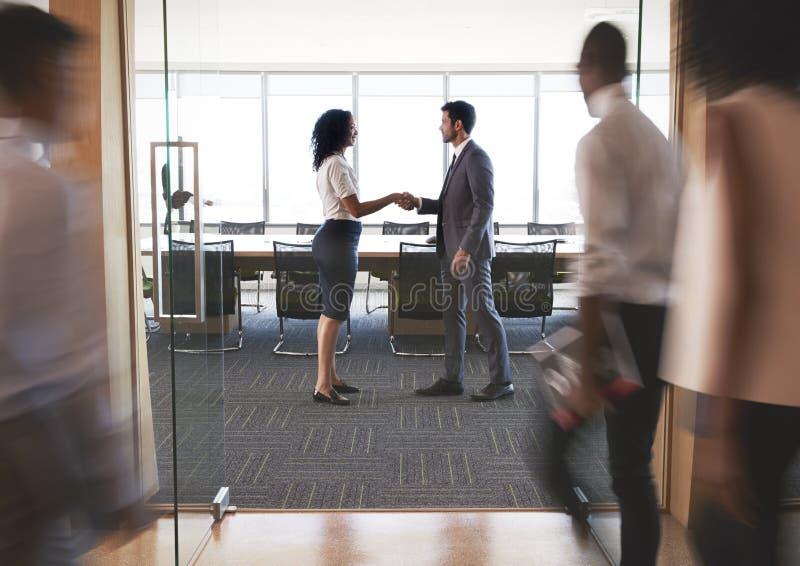 Empresários que agitam as mãos na entrada à sala de reuniões imagens de stock