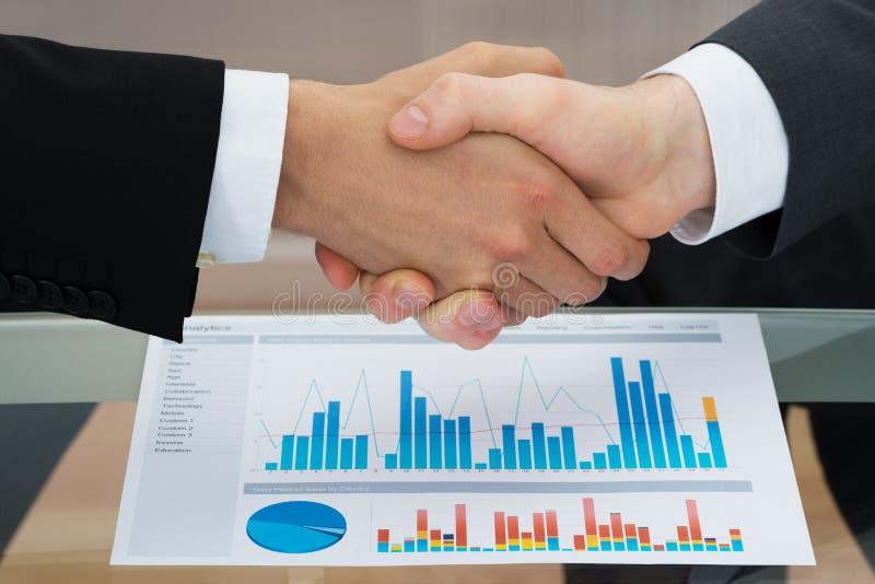 Empresários que agitam a mão na frente do gráfico imagens de stock
