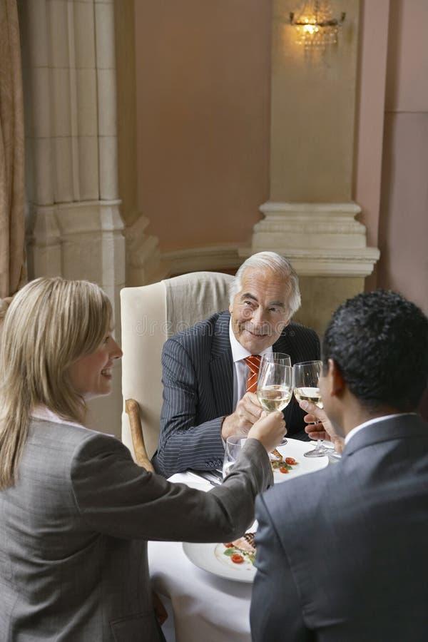 Empresários que brindam copos de vinho imagens de stock royalty free