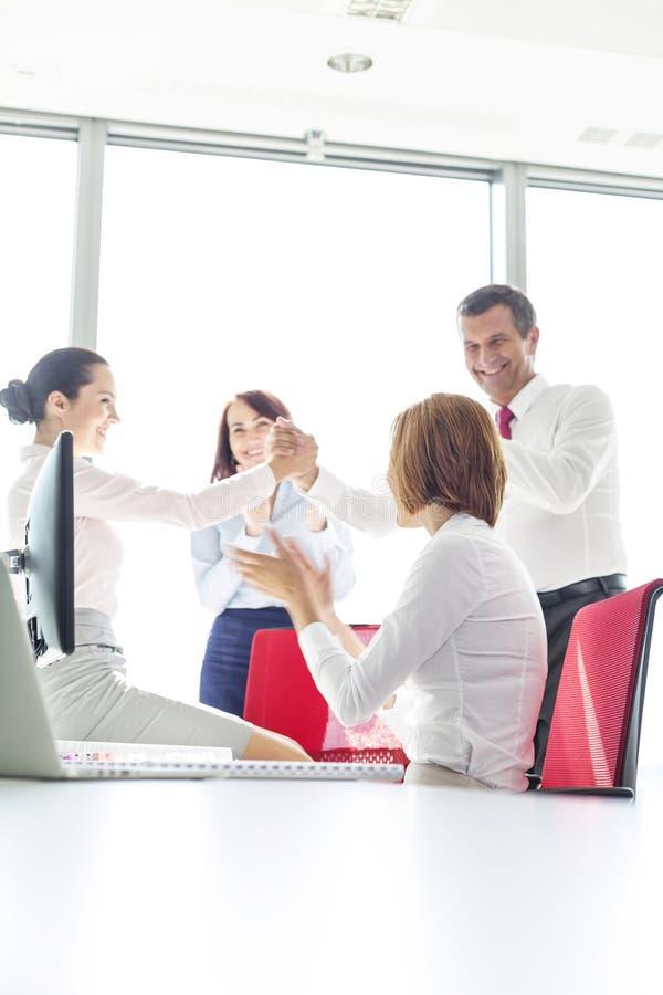Empresários que comemoram o sucesso no escritório imagens de stock royalty free