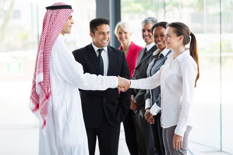 Empresários que dão boas-vindas ao homem de negócios islâmico fotografia de stock