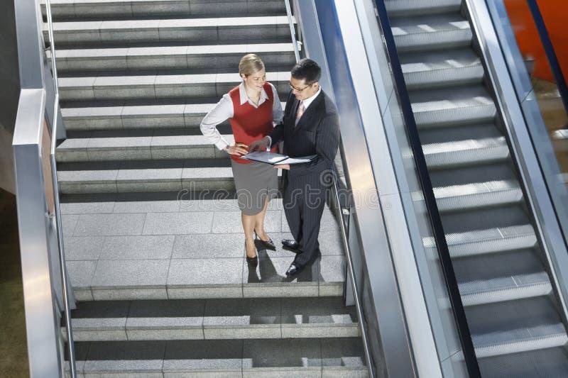 Empresários que discutem o trabalho em escadas imagens de stock royalty free