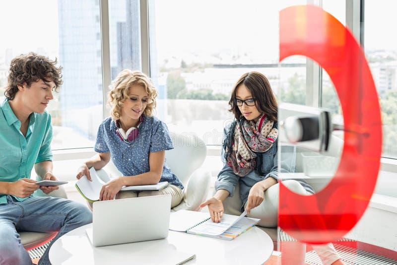 Empresários que discutem sobre o arquivo no escritório criativo fotografia de stock