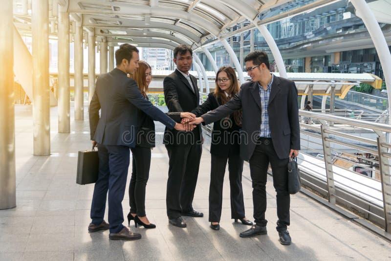 Empresários que empilham o conceito das mãos, dos trabalhos de equipa e planear fotos de stock