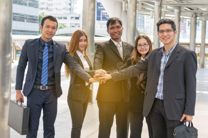 Empresários que empilham o conceito das mãos, dos trabalhos de equipa e planear imagem de stock