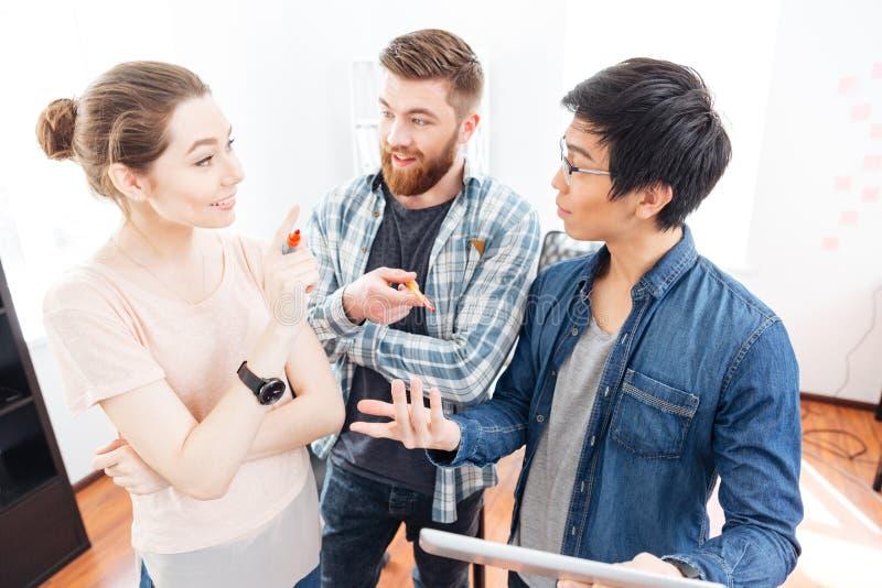 Empresários que estão e que discutem o plano do bisness usando a tabuleta no escritório imagem de stock royalty free