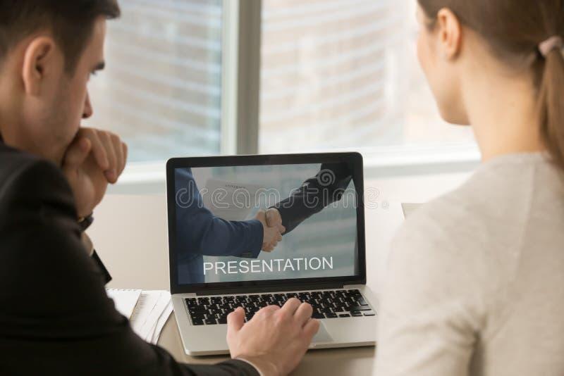 Empresários que olham a apresentação na tela do PC na reunião, imagem de stock