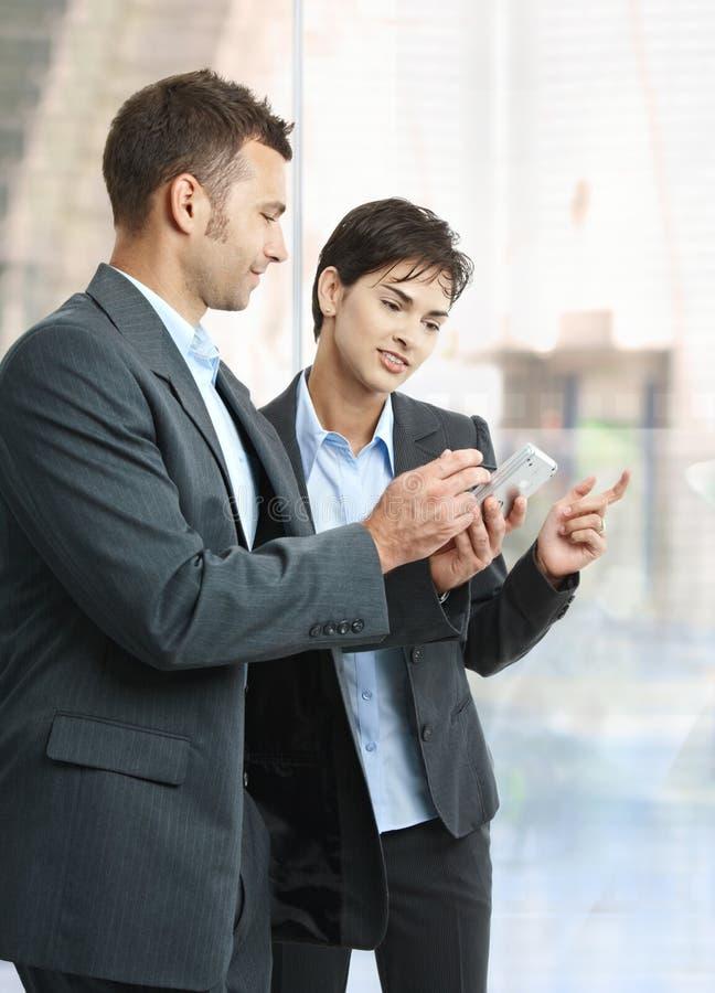 Empresários que olham o smartphone fotos de stock royalty free