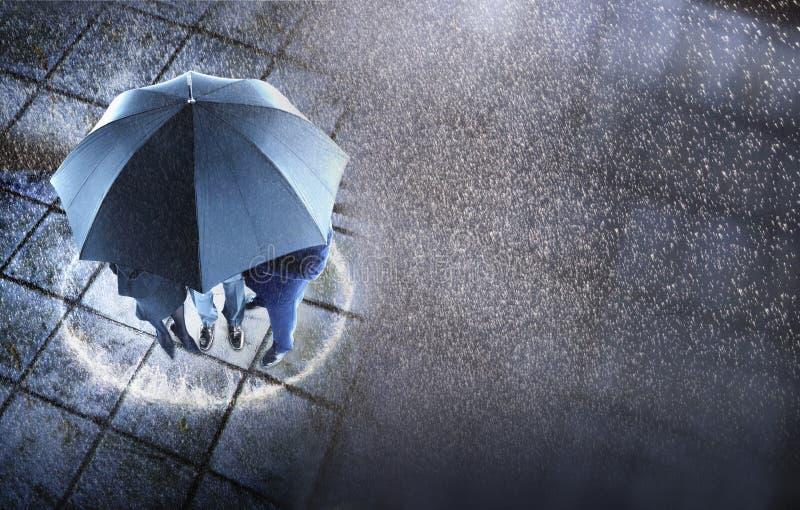 Empresários que protegem sob um guarda-chuva na chuva fotografia de stock