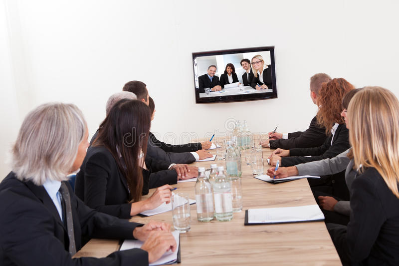 Empresários que sentam-se na tabela de conferência imagem de stock royalty free