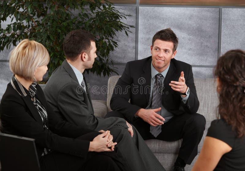Empresários que sentam-se no sofá, falando foto de stock royalty free