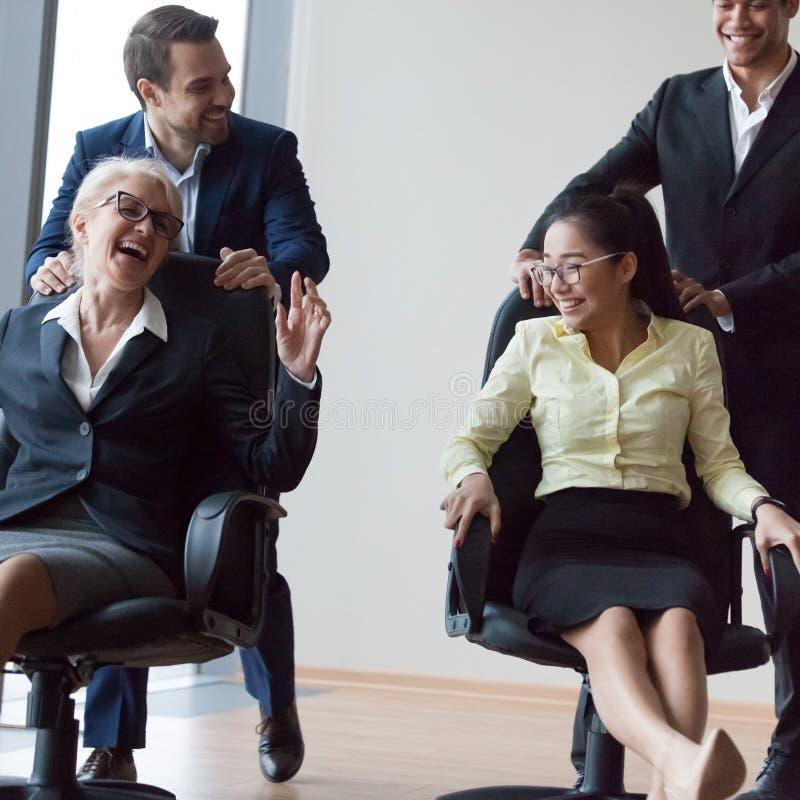 Empresários que têm a equitação do divertimento em cadeiras e que riem em offic imagem de stock royalty free