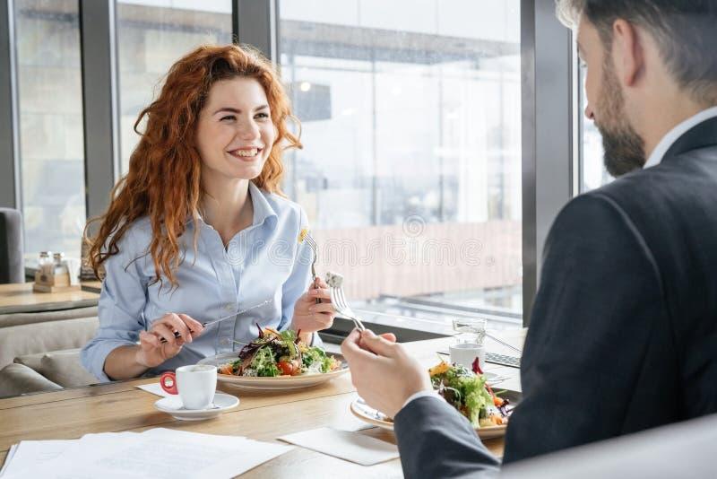Empresários que têm o almoço de negócio na fala bebendo de assento do café da salada comer do restaurante alegre fotos de stock