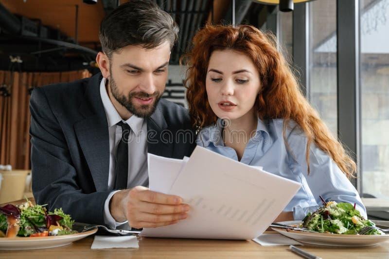 Empresários que têm o almoço de negócio no restaurante que senta-se comendo documentos da leitura foto de stock