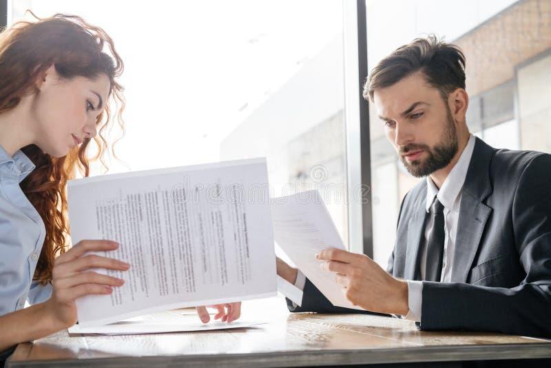 Empresários que têm o almoço de negócio no restaurante que senta-se olhando os documentos concentrados fotos de stock